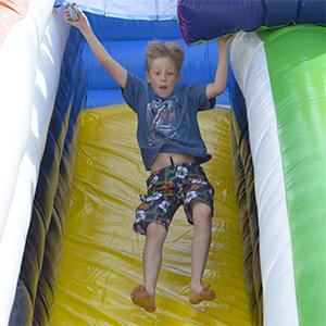 Boy jumping down bouncy castle slide